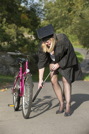 inflating: Mature student wearing cap and gown inflating cycle tyre