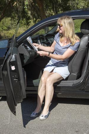 motorist: Woman motorist  reading a map