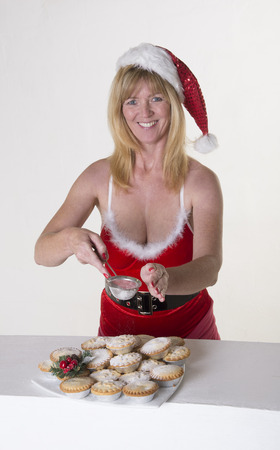 finishing touches: Woman in Santa outfit puts icing sugugar topping onto Mince Pies Stock Photo