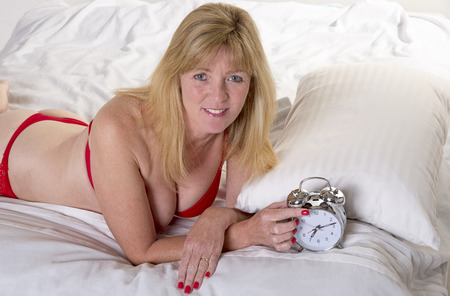 late forties: Woman laying in bed with alarm clock