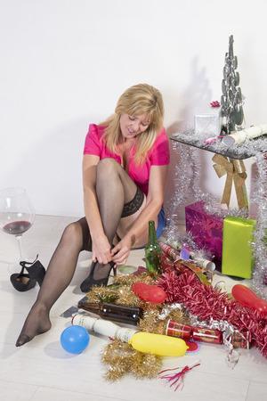 short skirt: Partygoer in short skirt taking her shoes off Stock Photo