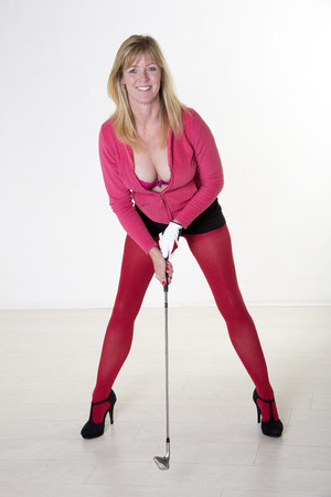 Attractive mid age female golfer wearing high heels photo
