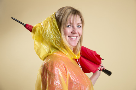 Woman in yellow poncho holding red umbrella Stock Photo