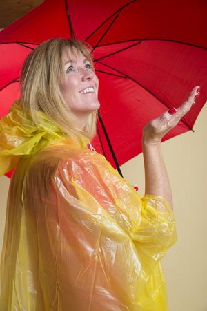 rainwear: Woman in yellow poncho holding red umbrella Stock Photo