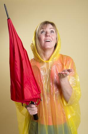 rainwear: Woman in Poncho holding an umbrella Stock Photo