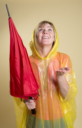Woman in Poncho holding an umbrella Stock Photo