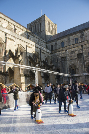 Christmas skaters on the ice rink at Winchester Cathedral Hampshire UK  earlier today. The temporary skating sessions are staged  by Winchester cathedral and Robin Cousins the famous ice skater 13 December 2014