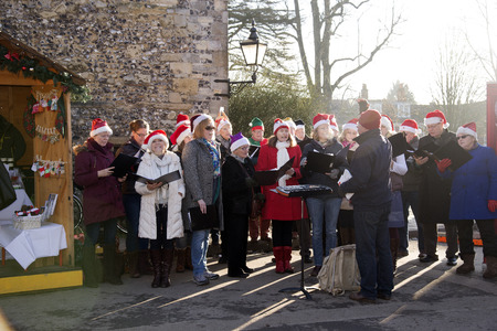 Carol singers performing in The Close Winchester Cathedral Hampshire UK earlier today. Singing Christmas carols are members of Winchester Musicals and Opera Society entertaining visitors to the Christmas Market 13 December 2014 Imagens - 34547069