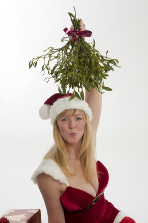 Woman blowing kisses in Santa outfit with bunch of Mistletoe at Christmastime photo