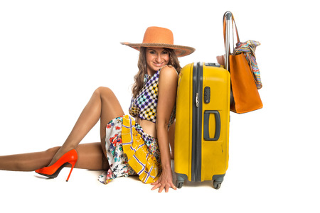 Woman sitting in summer dress with suitcase and handbag photo