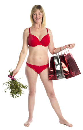Woman standing in red underwear with mistletoe and shopping bags photo