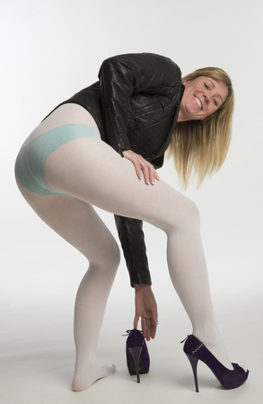 Woman in white tights putting on high heel shoes photo