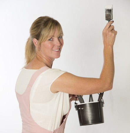 fuller figure: Woman wearing overalls holding paint brush