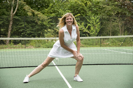 limbering: Sportswoman limbering up on a tennis court Stock Photo