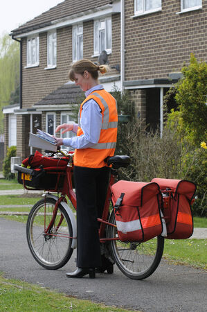 royal mail: Royal Mail postwoman sorting letters on her round