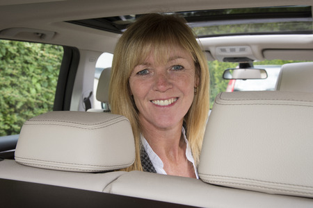 headrest: Portrait of a woman sitting in the rear seat of a car Stock Photo