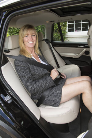 Woman in car wearing business suit adjusting seat belt Stock Photo