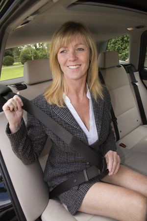 suited up: Woman in car wearing business suit adjusting seat belt Stock Photo