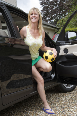 Woman getting out of a car holding a football Archivio Fotografico