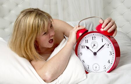 getting late: Woman in bed with ringing alarm clock Stock Photo