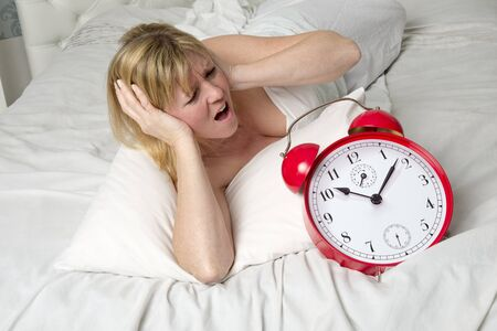 ringing: Woman in bed with ringing alarm clock Stock Photo