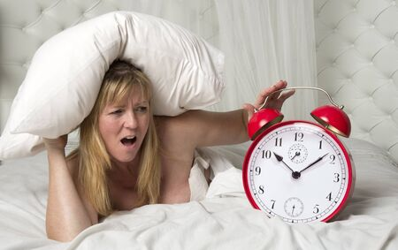 getting late: Woman in bed with head under pillow and a ringing alarm clock