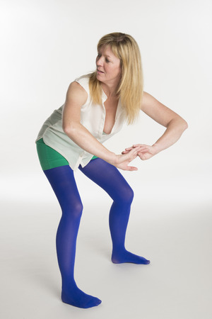 Woman in blue tights dancing a twerker dance