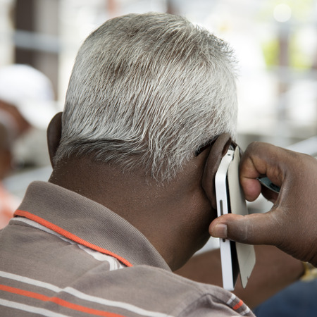 grey haired: Grey haired man using a mobile phone