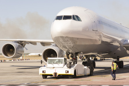 Passenger jet being towed by a tug