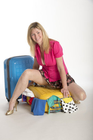 Woman trying to close her holiday suitcase photo