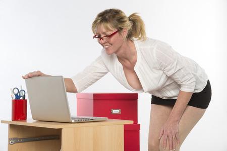 neckline: Sexy secretary with plunging neckline working at desk Stock Photo