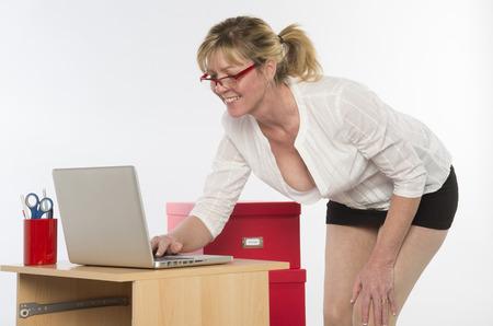 secretaria sexy: Secretaria atractiva con escote profundo trabaja en el escritorio