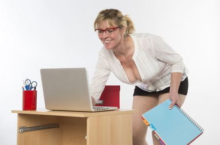 sexy secretary: Sexy secretary with plunging neckline working at desk Stock Photo
