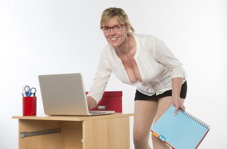 secretaries: Secretaria atractiva con escote profundo trabaja en el escritorio