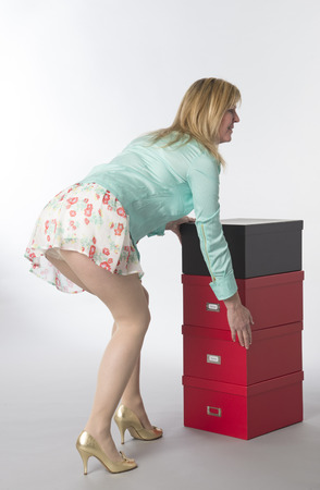 Office worker bending and moving boxes