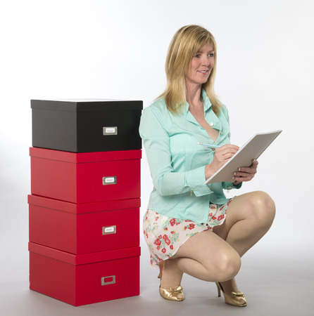sexy secretary: Female office worker checking and stacking file boxes