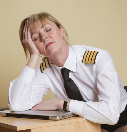 fatigued: Tired female airline pilot wearing insignia of a captain Stock Photo