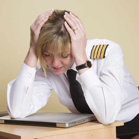 Tired female airline pilot wearing insignia of a captain Archivio Fotografico
