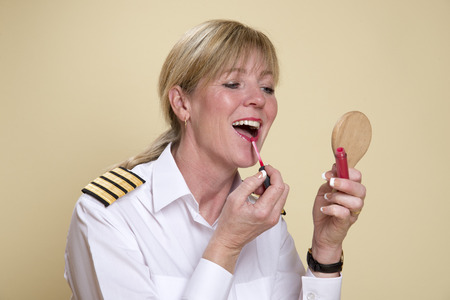 personal grooming: Female airline pilot applying lipstick makeup Stock Photo