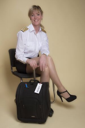 personal grooming: Attractive female airline pilot waiting to go on shift Stock Photo
