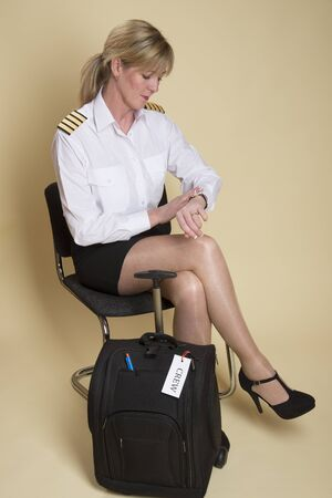 personal grooming: Attractive airline pilot checking her watch and the time before going on shift