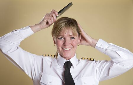 personal grooming: Attractive airline pilot combing her hair