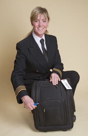 personal grooming: Female airline pilot checking contents of her flight bag