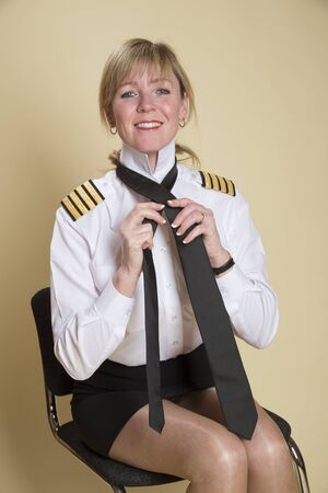 personal grooming: Female airline pilot tying a black necktie