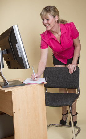 secretary skirt: Secretary in an office with computer screen Stock Photo