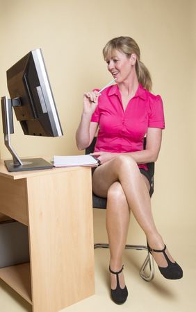 secretarial: Secretary in an office with computer screen Stock Photo