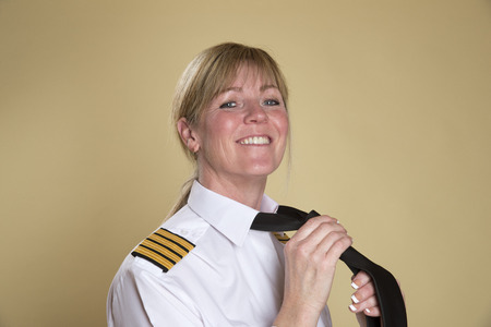 personal grooming: Female airline captain tying her necktie knot Stock Photo