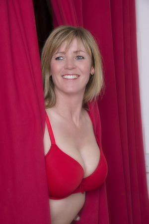 Woman in red bra peering through a red curtain