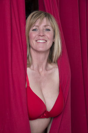 busty bra: Woman in red bra peering through a red curtain