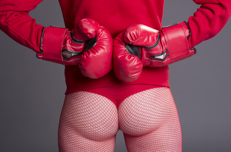 fishnets: Woman fighting fit and wearing red boxing gloves